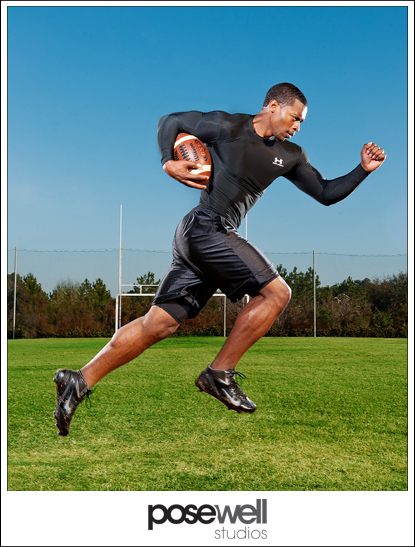 Photograph of athlete running with a football